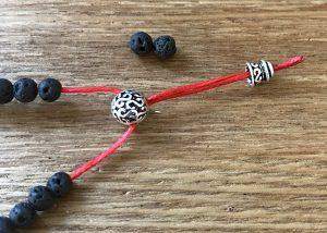 数珠パーツのボサに2本の紐を挿し入れます